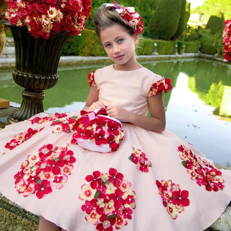 Girls beautiful pale and dark pink dress by Lesy Luxury Flower. Made from a lightweight cotton matte satin, it is decorated with hydrangea flowers in different tones of pink. With a fitted bodice, it has capped sleeves and a full gathered skirt with layers of stiff tulle lining under. Fully lined in a soft, lightweight cotton for comfort, there is a double satin and grosgrain ribbon belt that can be tied at the front or back of this very special dress.