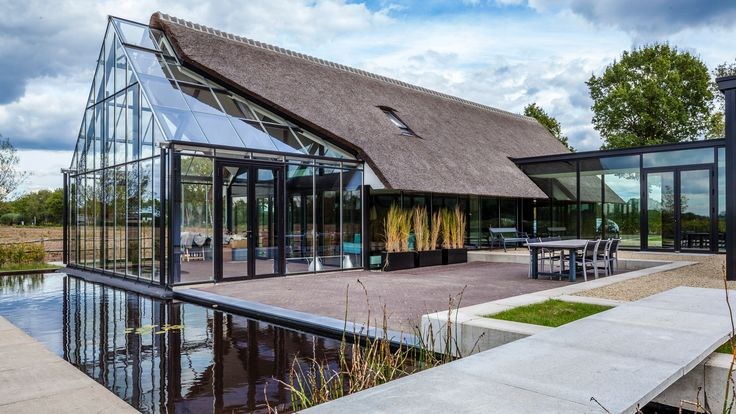 Cottage meets greenhouse in modern thatched home - Curbedclockmenumore-arrow : This H-shaped Dutch home features walls of glass topped with a traditional gable roof