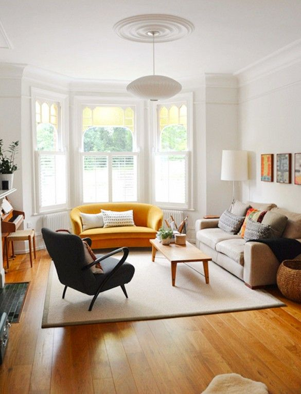 A yellow sofa is put in a traditional living room of neutrals and whites, with a wooden bench as coffee table, black armchair and white hanging light
