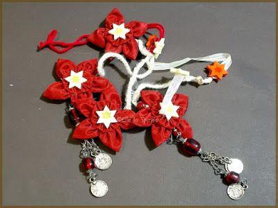 Ghirlandina natalizia per il lampadario fatta con fiori di stoffa, vecchi orecchini, fili di lana e stelline adesive.