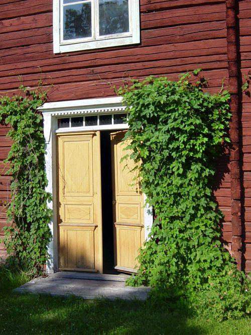 "Erik-Anders Hälsingegård, Asta (Unesco: ""Decorated Farmhouses of Hälsingland"") - light yellow ochre double front door - red timber walls - white wooden frames - green hop."