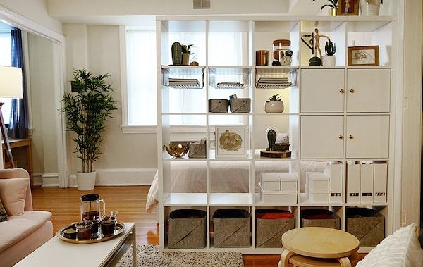A White Kallax Bookshelf With Boxes And Doors Is Used As A Room