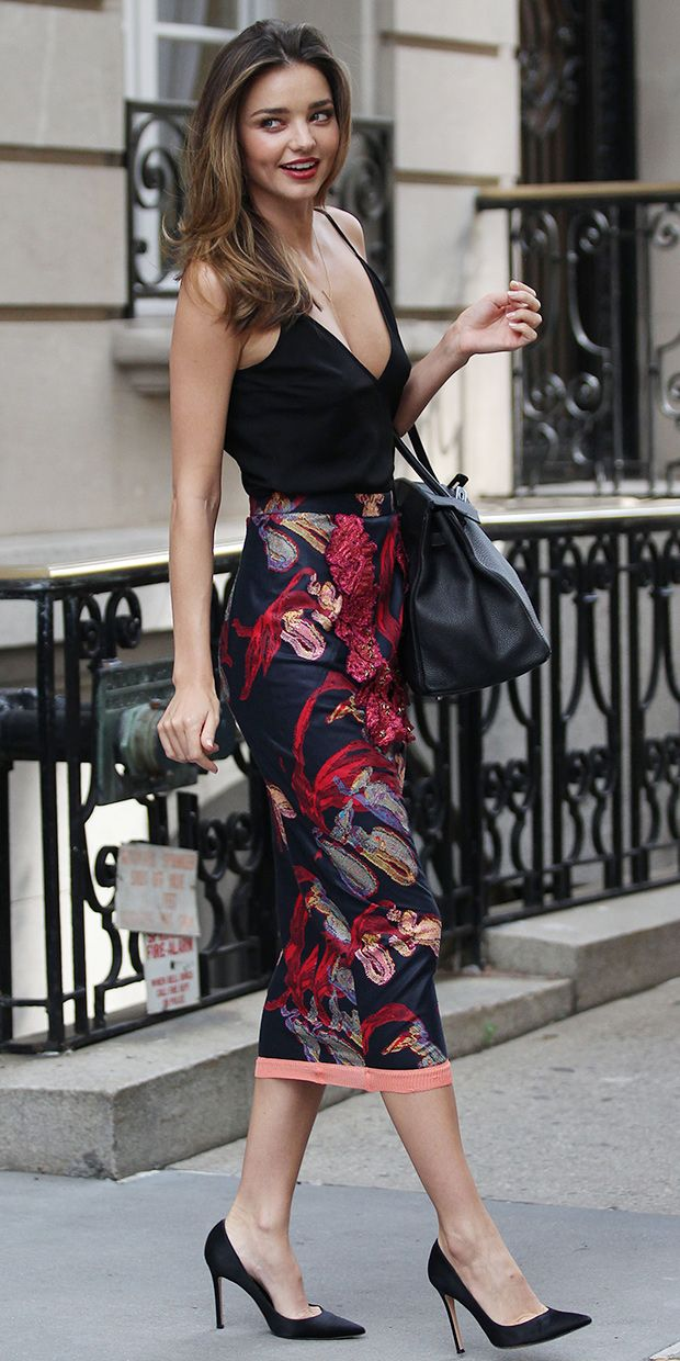 Miranda Kerr wears a black camisole, printed pencil skirt, and black pumps