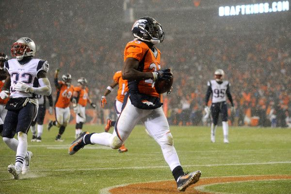 Running back Ronnie Hillman #23 of the Denver Broncos scores a second quarter touchdown past free safety Devin McCourty #32 of the New England Patriots at Sports Authority Field at Mile High on November 29, 2015 in Denver, Colorado.