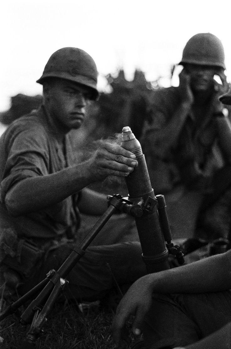 Soldados dispara um morteiro 60 milímetros M2 capturado, originalmente uma arma produzido pelos Estados Unidos para uso na Segunda Guerra Mundial e na Guerra da Coreia. O morteiro foi capturado em uma patrulha em uma plantação de arroz, das forças vietcongues. Nomes, data e local desconhecidos.