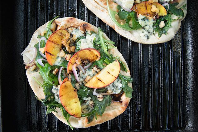 Grilled Blue Cheese and Arugula Flatbread with Peaches: Drizzled with vinegar, these pitas are topped with grilled peaches, creamy blue cheese, and crunchy walnuts for an easy and delicious appetizer or lunch.