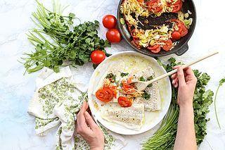 Pieczony dorsz z czosnkiem, pomidorami, porem i świeżą kolendrą