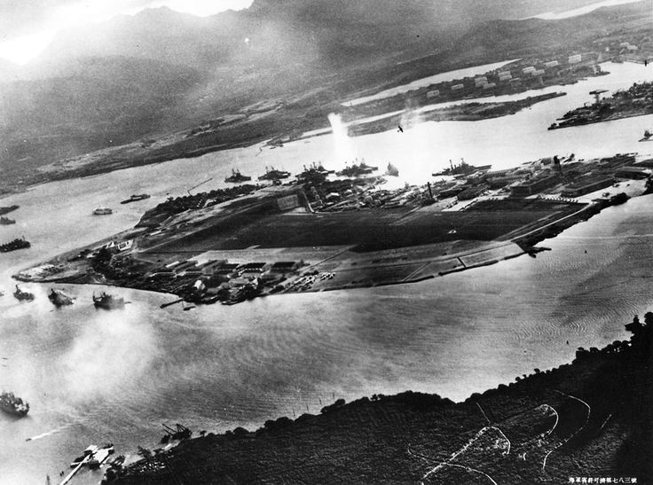 Japanese aircraft can be seen in the air above Pearl Harbor (top center and upper right) in this captured Japanese photograph taken during the initial moments of the Japanese attack.