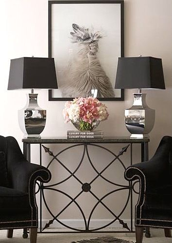 A lovely, detailed console table is placed between two black chairs with silver nailhead trim that matches the twin silver lamps with black shades