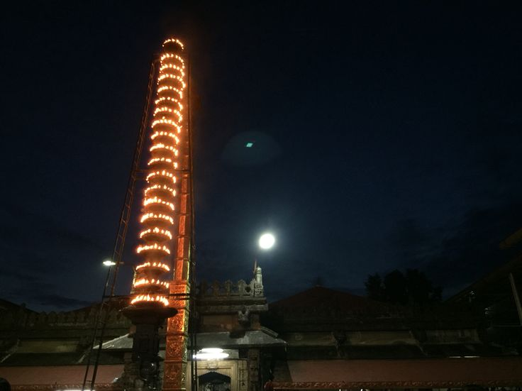 Fully lit lamp post twinkles with hundreds of lamps. At Kollur Mookambika temple