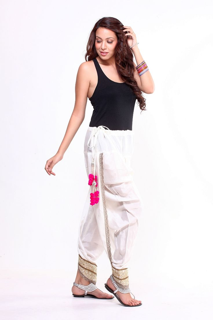 These snazzy overlapped dhoti pants with tie up belt. Its an Indian dhoti made easier to wear in salwar form with colourful tassels for the bohemian look. Intricate cutwork cuffs and lace all over make these dhoti pants extremely feminine and special. Can be teamed up with tops, spaghettis, tunics, kurtas and even jackets.  Material:  Cotton Shantoon