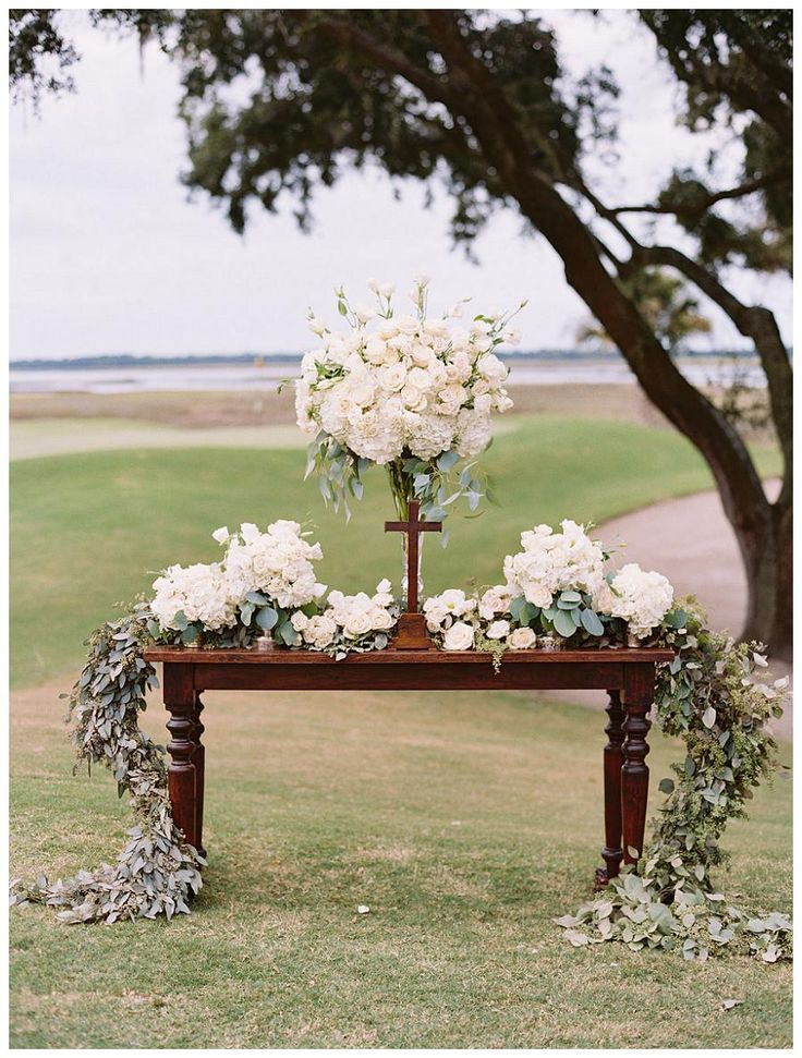 Outdoor wedding ceremony altar table with white florals and garland. Overlooking The River Course at the Kiawah Island Club in SC. Florals and design by Bella Flora, image by Landon Jacob.