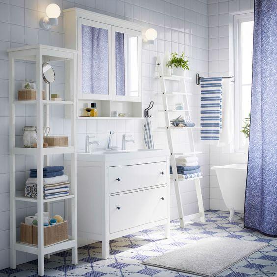 Baño blanco con armario para lavabo, estante y armario de espejo HEMNES blancos, cortina de ducha azul y toallas azules y blancas.: