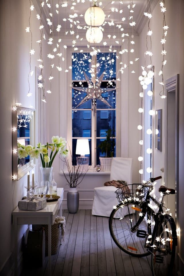 The holidays are almost here, and if the more traditonal combos of red and green or blue and silver aren't your ideal color schemes, you can still add some festivity to your decor by taking it in a more neutral, simple-chic Scandinavian-inspired direction. One way to do that is with strands of simple white lights. If you still want a bit of color, natural elements like greenery and branches are the perfect complement to twinkling lights.