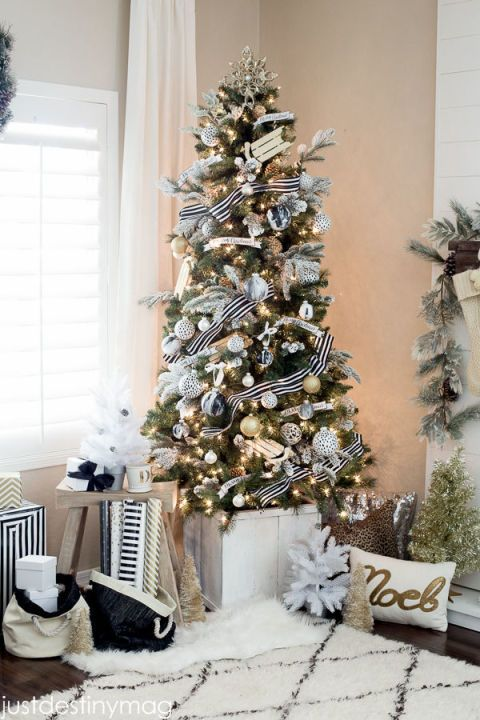 Black-and-white striped ribbon wraps around a Christmas tree that's adorned with flocked branches and faux marble ornaments. See more at Just Destiny.: