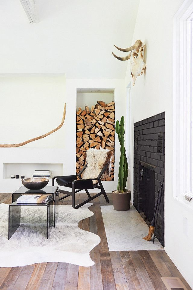 Scandinavian living space with a black fireplace, stacked firewood, an indoor cactus, a cowhide rug, and a modern black leather chair