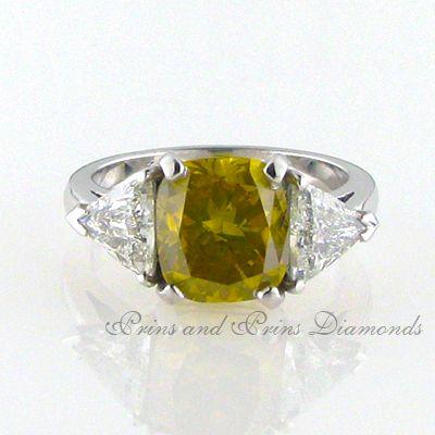 The centre diamond is a 4.031ct SI3/vivid fancy yellow cushion cut diamond with 2 = 1.43ct HI/SI trillion cut ddiamonds set in 18k white gold