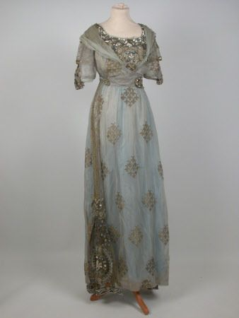 Silk silver gauze gown with woven pattern in gold. Straight style with high waist. Short sleeves with tie effect, inlet panels of gold net. Stomacher panel of gold net sewn with glass beads silver cord, artificial pearls and pastes. Epaulettes of fine crepe cross over effect on front bodice with paste metal buckle. Fastens at back; fastenings are partly concealed by panel of gold net as front.