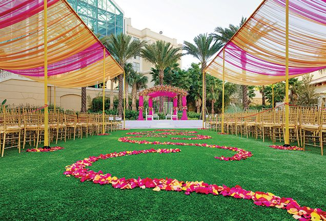 A Vibrant Indian Wedding in LA | Go beyond the traditional arrangements and opt for intricately placed, interwoven orange and fuchsia flower petals to lead you down the aisle. At the end, a flower-covered mandap makes a grand statement.