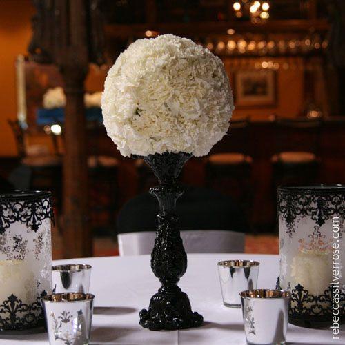 White carnation pomander displayed on black glass candleabara