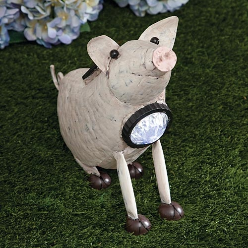 """Charming Solar Pig, Item #47063, $9.99    Our adorable pig sculpture will light up at dusk with a blue LED in a faceted lens at his collar. Skillfully crafted of sheet metal and antiqued with a blush undertone, this little guy will add a bit of country personality to your patio or garden. Solar panel recharges in the sun, complete with an on-off switch. Measures 12"""" long x 9½"""" tall x 3"""" wide."""