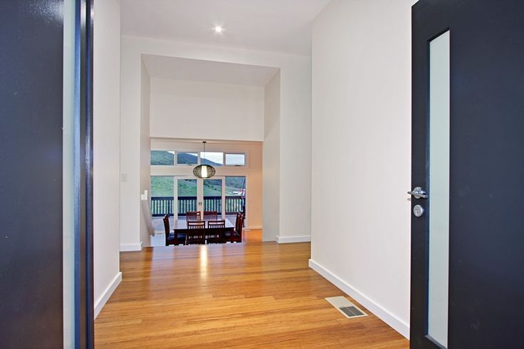 This hallway of a Sloping Block/Contemporary Weatherboard home with Timber floorboards shows just how well you can utilise a Sloping block.