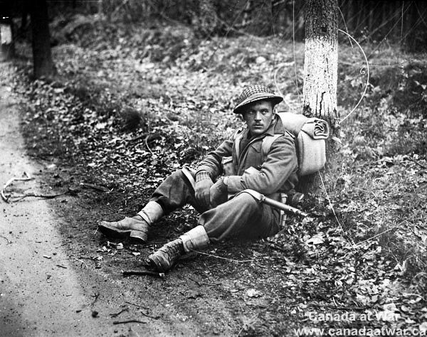 The Netherlands - Private N.J. Ingram, Perth Regiment, stops for a rest north of Arnhem, Netherlands, 15 April 1945.
