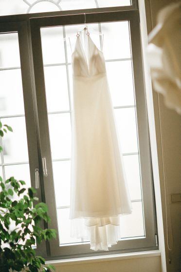 Easy wedding dress hanging in the window.