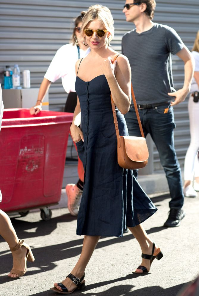 Sienna Miller in a navy dress with tan sunglasses, a Mansur Gavriel purse and black sandals
