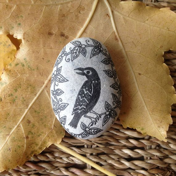 a hand-drawn crow on a small blueish-white stone from a beach in the south of england. it is approximately 4.5cm across its length and fits nicely