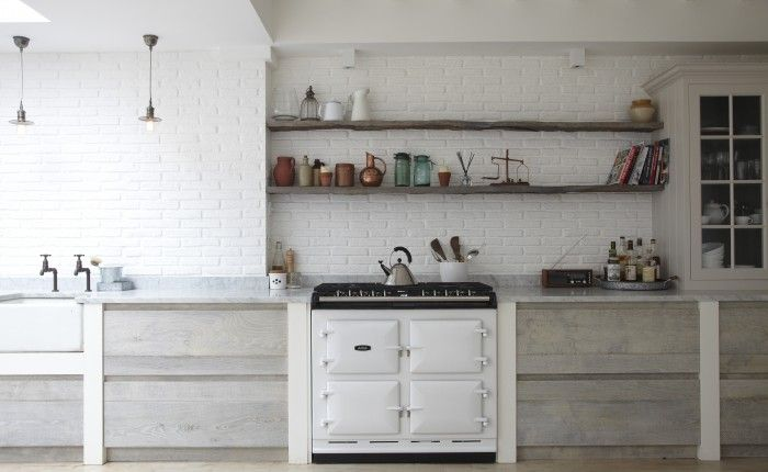 White brick walls, light wood cabinets + reclaimed wood shelves