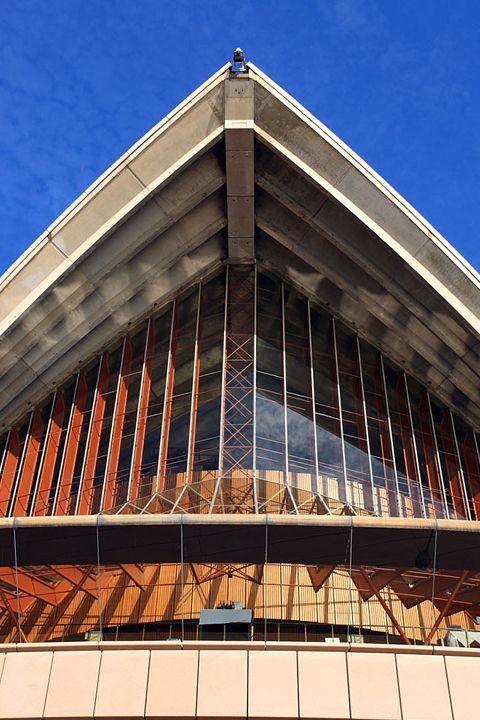 The glass wall was built after Utzon resigned from the project, in line with his vision of 'its feeling of hanging from the shell'. The glass walls offer a wondrous view from the main foyers, out across Sydney Harbour. http://www.guiddoo.com/