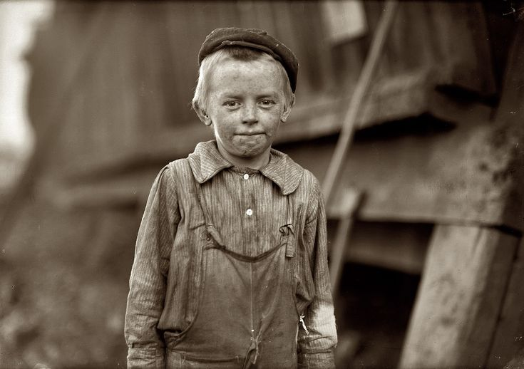 """November 1910. Birmingham, Alabama. """"Our baby doffer"""" they called him. Donnie Cole. Has been doffing for some months. When asked his age, he hesitated, then said, """"I'm twelve."""" Another young boy said, """"He can't work unless he's twelve."""" Photo and caption by Lewis Wickes Hine."""