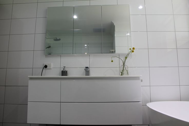 Having a mirrored cabinet rather than a mirror above your vanity adds extra space. This entry chose a darker tile grout so their white tiles really popped. It works in with their wall hung vanity too.