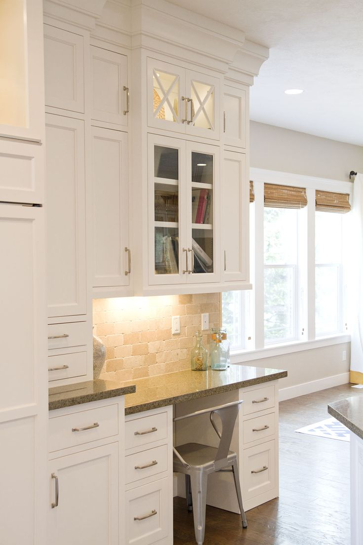 kitchen cabinetry - love the crisscross design over the glass top and the crown moulding look near the ceiling