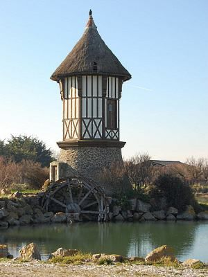 Lower Normandy region of northwestern France. The  storybook  structure  pictured  above,  right, is a mill located in Cour-  seulles-sur-Mer. It features a stone base with stucco and half-timbering on the upper level. Crowning this architectural gem is a thatch roof.