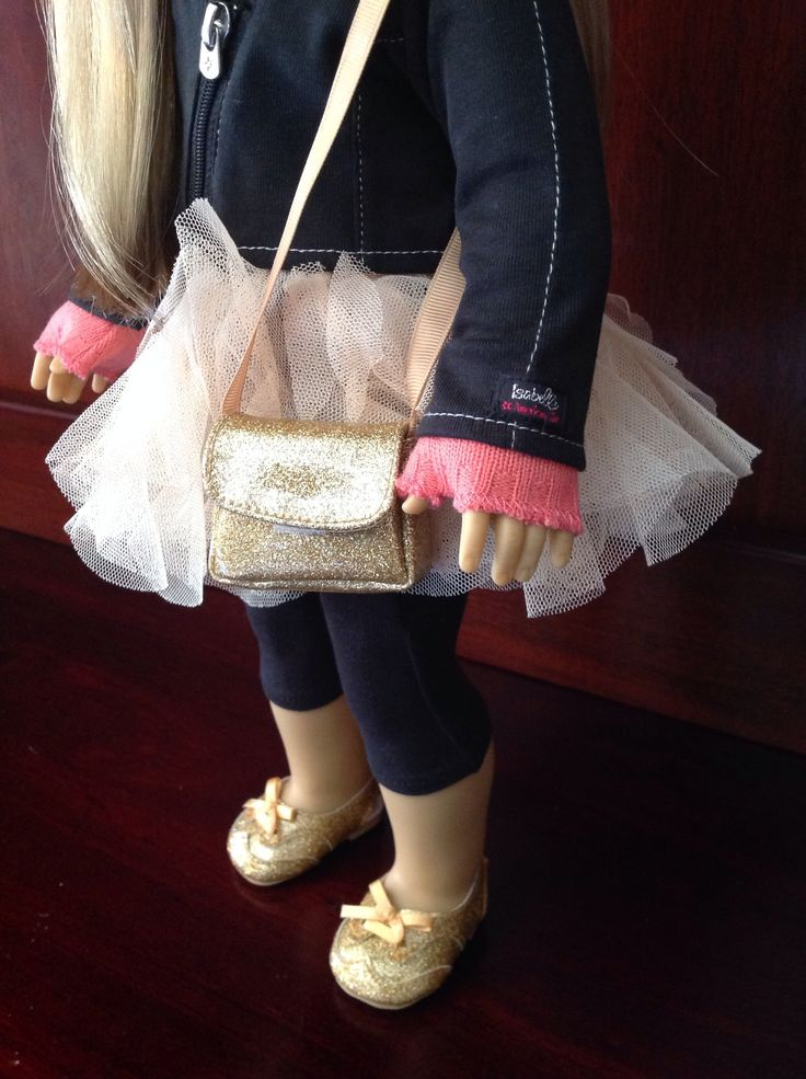 American Girl Isabelle wearing gold meet shoes with her accessories and performance sets.
