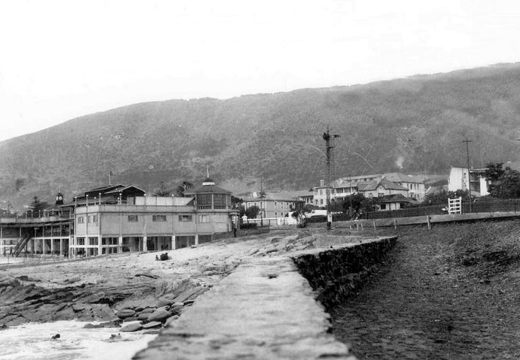 """Sea Point Baths and Rail Line. 1923. The clock on the Pavilion was provided by E.Burmester, the Jeweller, Watchmaker and Optician of Adderley Street. His Will, dated 3 October 1914 stated: """"In grateful remembrance of the very pleasant times I had at Sea Point, I determine that my heirs shall erect there on the beach, a fine clock tower to the value of two hundred to three hundred pounds sterling."""