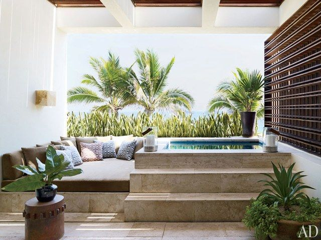 The actor's master bath terrace, shaded by a parota brise-soleil, has a travertine Jacuzzi lined in blue mosaic tiles; the side table is by Tucker Robbins, and the lanterns are by Casamidy.