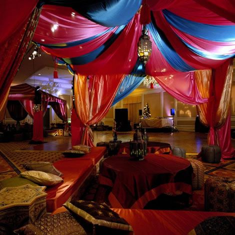 Add drapes and cushions in shades of royal blue red for Arabian party decoration ideas
