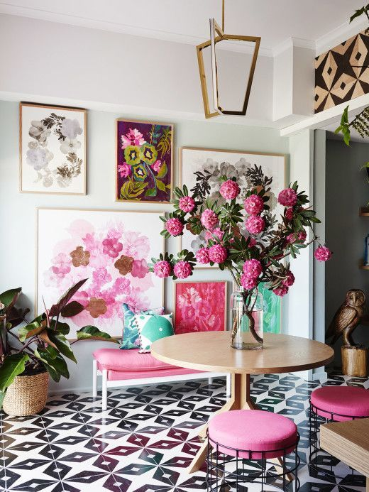 Sophisticated, Vibrant Living Space with Graphic Wall Prints and Classic Floral Arrangement