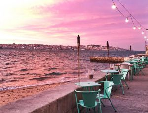 Mesas do restaurante Atira-te ao Rio, com vista para Lisboa, ao fundo.