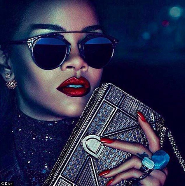 Red lips and tips: This image focuses on the 27-year-old's bold accessories; in addition to her bold red lipstick and nail polish, Rihanna can be seen wearing a pair of black sunglasses while carrying an embellished purse