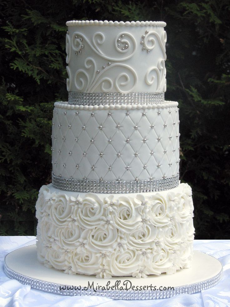 - 3-tier all-white wedding cake decorated with buttercream rosettes, quilting and scrolling, and accented with silver pearls and glam ribbon.