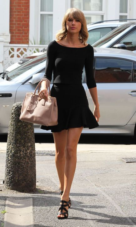 Taylor Swift wearing a Guess top and skirt