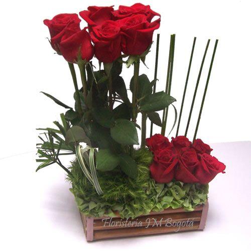 Con solo 12 rosas es posible armar un lindo arreglo. Se han dejado 6 en un nivel mas alto, todo insertado en una base de madera y con algunos adornos verdes que hacen contraste con el rojo de la rosa. Para enviar a Bogota a domicilio. Arreglo Floral en Dos Niveles de 6 Rosas: USD$48