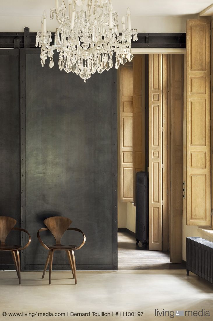 Two chairs against black sliding door in room with chandelier and panelled window shutters
