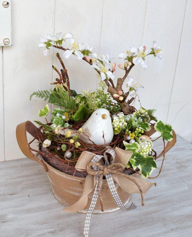 Liebevoll dekorierter Metalltopf mit Frühlingsblühern,Vogelnest,Keramikvogel,Moos,Ästen und etwas Kordel. Topf:21x10cm Vogel ca.9x7cm Gesamthöhe ca.28cm