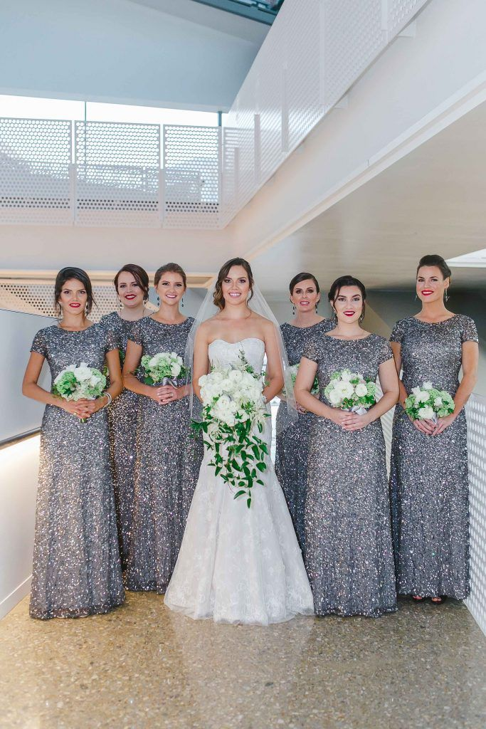 Bride with bridesmaids in long cap sleeved silver sequin dresses with white and green wedding bouquets before fall wedding at Perot Museum in Dallas, Texas - Photos by Katherine O