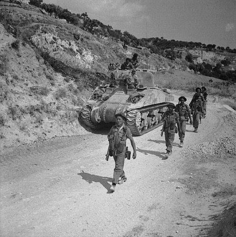 Personnel of Princess Patricia's Canadian Light Infantry advancing past a Sherman tank, near Valguarnera, Italy, July 19, 1943 / Des membres du Princess Patricia's Canadian Light Infantry passent devant un char Sherman près de Valguarnera (Italie), le 19 juillet 1943